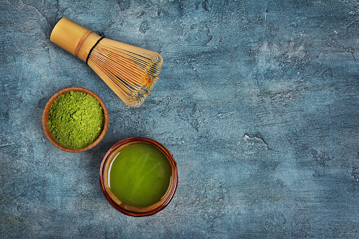 Top view on organic green matcha tea powder in bowls with bamboo whisk