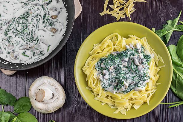 top view on pasta with spinach, cream and champignon mushrooms - huhn spinat pasta stock-fotos und bilder
