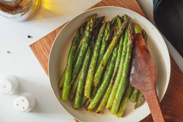 Top view on roasted asparagus in a white pan on a kitchen table. Modern style, vegetarian food. stock photo