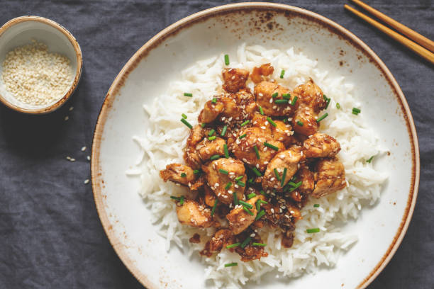 Top view on sesame chicken pieces with rice on a ceramic plate. Chinese traditional dish. stock photo