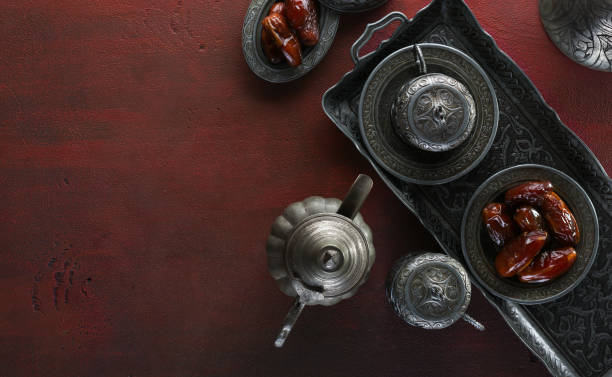 top view on silver plate with date fruits and coffee cups on the dark red wooden background. ramadan background. ramadan kareem. - eid stock pictures, royalty-free photos & images