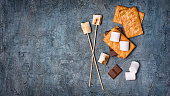 istock Top view on sticks with roasted on campfire marshmallow, crackers and chocolate as ingredients for s'mores 1085565358