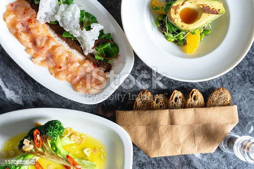 istock Top view on tasty luxury food with restaurant food styling on marble table. Fresh and grilled vegetables salads with avocado, broccoli and sea bass ceviche in white plate. Food photography background 1170885645