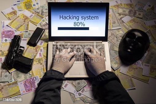 istock Top view on the hands of an attacker programmer hacking a data server from his laptop. Money is thrown on the table, lies a telephone, a gun, and a mask. 1167201526