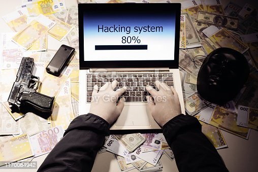 istock Top view on the hands of an attacker programmer hacking a data server from his laptop. Money is thrown on the table, lies a telephone, a gun, and a mask. 1170084942