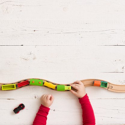 Top view on toy wooden trains on railway on white wooden table background. Child's hands playing with educational toys.