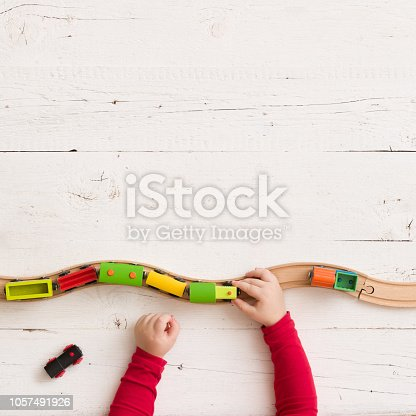 istock Top view on toy wooden trains on railway on white wooden table background. Child's hands playing with educational toys. 1057491926