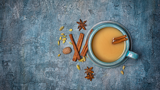 Top view on traditional indian drink masala chai tea with milk and cinnamon stick, green cardamom, anise star and nutmeg