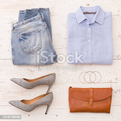 Top view on woman's fashion clothes: blue jeans, shirt, heels, leather clutch and accesories on white wooden background.