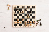 Top view on wooden chess board with figures during the game on white wooden table background
