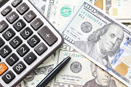 Business, finance, investment, accounting, taxes or money exchange concept : Top view or flat lay of calculator and pen on American Dollars cash money