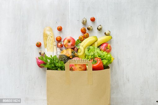 istock Top view paper bag of different fresh health food on white wooden background. Top view. Flat lay 898551624