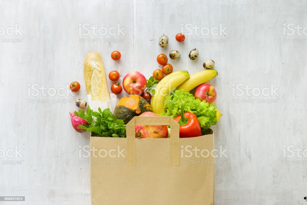 Top view paper bag of different fresh health food on white wooden background. Top view. Flat lay stock photo