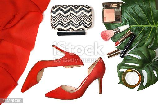 1078252566 istock photo Top view party outfit red shoes, accessories makeup cosmetics, clutch, tropical monstera leaves on white background isolated. 1155254381