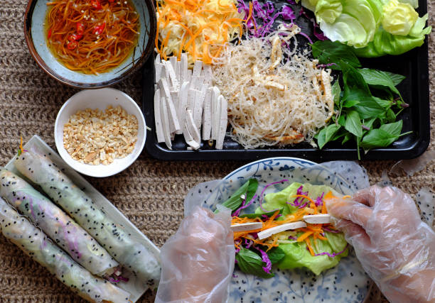 Top view people hand making vegan rice paper rolls stock photo