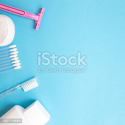 istock top view personal care products. white bottle, pink razor, ear sticks, cotton pads, toothbrush on blue background. copy space 1027116350