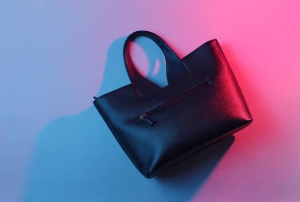 foto von modischer lederhandtasche, blau-rotes neonlicht - neontasche stock-fotos und bilder