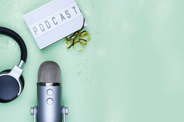 Top view photo of podcast concept - lightbox with letters podcast on it, headphones and professional microphone Top view photo of podcast concept - lightbox with letters podcast on it, headphones and professional microphone on the table producer stock pictures, royalty-free photos & images