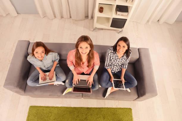 Foto de la vista superior de tres niñas con un ordenador portátil y tableta digital - foto de stock