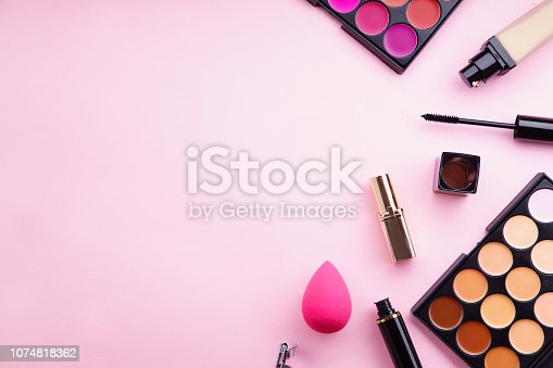 istock Top view picture of makeup products: lipstick and concealer palettes, foundation, mascara and eyelash curler on pink background. Feminine accessories concept 1074818362