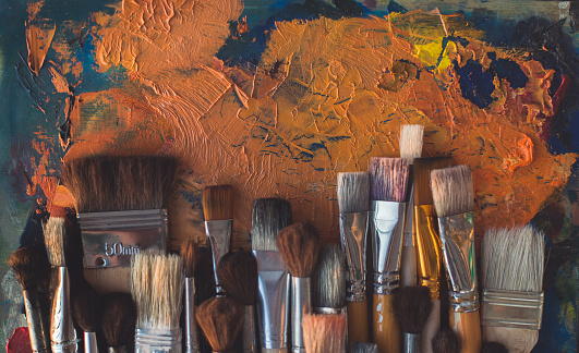 Top view picture of wooden paintbrush set different size with old palette on the background.