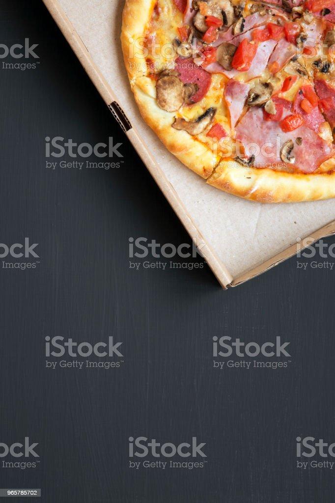 Bovenaanzicht, pizza met spek, tomaten, salami, kaas en champignons in een kartonnen doos op een donkere achtergrond. Kopieer ruimte. Van bovenaf plat lag. - Royalty-free Avondmaaltijd Stockfoto