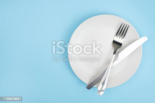 Top view plate with a spoon on the blue background.