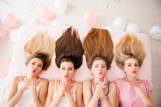 Portrait de la vue de dessus des meilleurs, nice, domestiques, positives, charmantes filles allongé sur le lit avec les cheveux en regardant à la caméra, réunion bénéficiant, week-end indoor, soufflant de l'air baiser avec palm - Photo