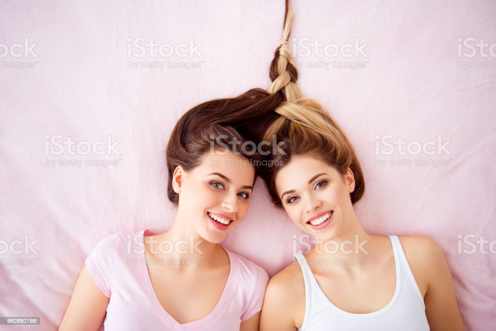 Top view portrait of charming, stylish, cheerful, joyful, cute, nice, successful  girls with pigtail from their hair lying on bed looking at camera spending time, together forever, trust, support royalty-free stock photo