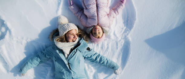 Top view portrait of cheerful mother with small daughter lying in snow in winter nature. stock photo