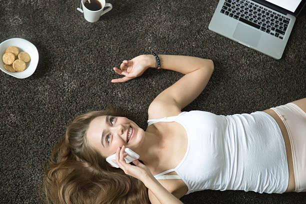 top view portrait of woman lying, talking on her phone - hipster unterwäsche stock-fotos und bilder