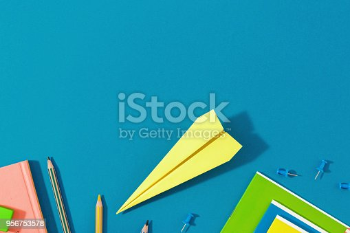 istock Top view school background. Flat lay back to school concept with paper airplane and school supplies on blue background 956753578