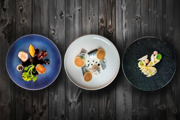 seleção de vista superior de requintados pratos de jantar na mesa de madeira - fine dining - fotografias e filmes do acervo