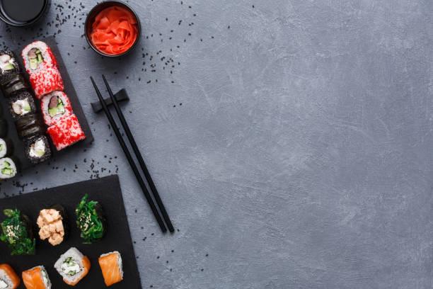 寿司マキと素朴なグレーとごま背景ロールのトップ ビュー セット - 日本食 ストックフォトと画像