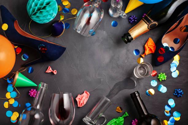 Vue de dessus tourné d'après une célébration de la fête avec le verre des bouteilles vides, vin, fille chaussures et décoration de fête - Photo