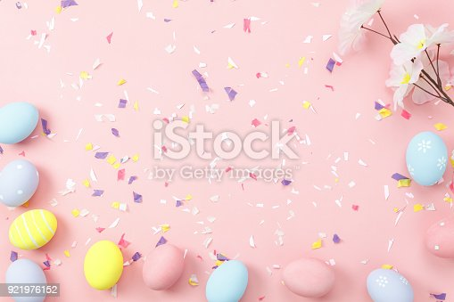 istock Top view shot of arrangement decoration Happy Easter holiday background concept.Flat lay colorful bunny eggs with accessory ornament on modern beautiful pink paper at office desk.Design pastel tone. 921976152