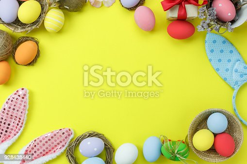 istock Top view shot of arrangement decoration Happy Easter holiday background concept.Flat lay colorful bunny eggs with accessory ornament on modern beautiful yellow paper at office desk.Design pastel tone. 928438440