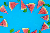 istock Top view, sliced watermelon fruit with many mints leaves on the old blue wooden table for background, wallpaper, and backdrop 1257052231