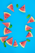 istock Top view, sliced watermelon fruit with many mints leaves on the old blue wooden table for background, wallpaper, and backdrop 1257052257
