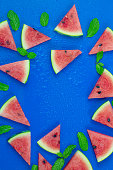 istock Top view, sliced watermelon fruit with many mints leaves on the old blue wooden table for background, wallpaper, and backdrop 1257052271
