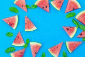 istock Top view, sliced watermelon fruit with many mints leaves on the old blue wooden table for background, wallpaper, and backdrop 1257052283