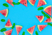 istock Top view, sliced watermelon fruit with many mints leaves on the old blue wooden table for background, wallpaper, and backdrop. 1273638769