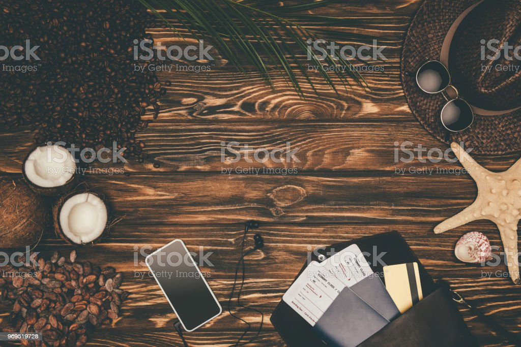 top view smartphone and flight tickets surrounded with various tropical travel attributes on wooden surface stock photo