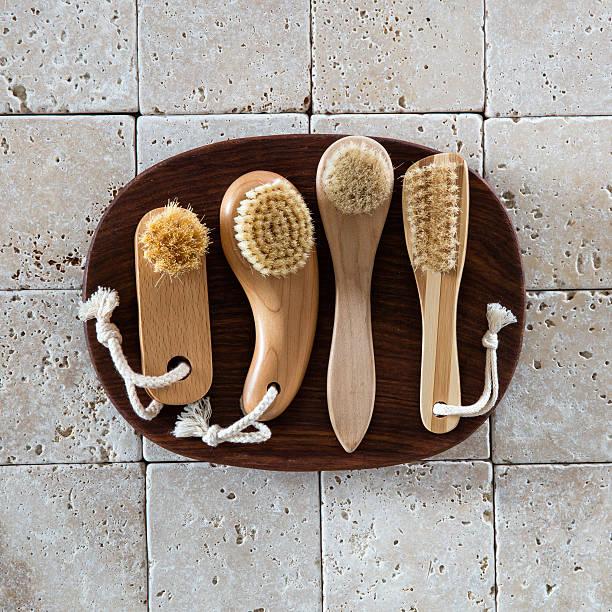 top view, stimulating brushes on limestone background for wellbeing concept - peeling bürste stock-fotos und bilder