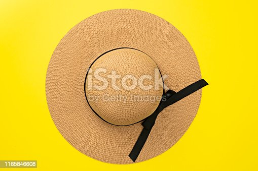 Top view straw hat with ribbon and bow on pastel yellow background. Beach accessory. Fashion  summer concept. Flat lay.