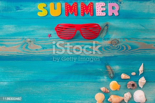 istock Top view summer holidays background concept with louvered shades and seashells on blue wooden table 1139300462