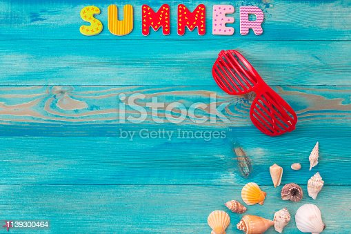 istock Top view summer holidays background concept with louvered shades and seashells on blue wooden table 1139300464