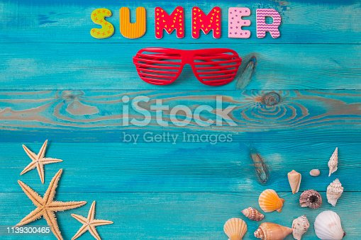 istock Top view summer holidays background concept with louvered shades, seashells and sea starfish on blue wooden table 1139300465