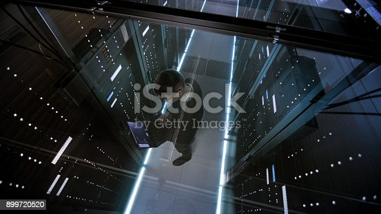 802317162istockphoto Top View Through the Glass of IT Engineer Working with Laptop in Data Center Full of  Active Rack Servers. 899720520