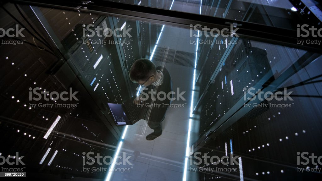 Top View Through the Glass of IT Engineer Working with Laptop in Data Center Full of  Active Rack Servers. stock photo